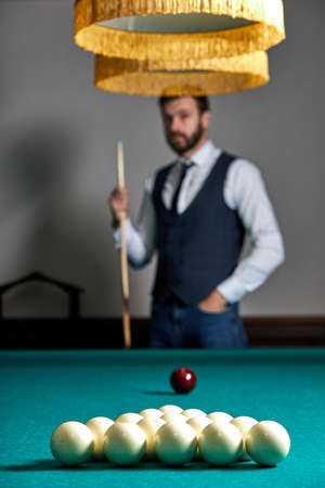 close-up photo of billiards balls on table, focus on white balls, handsome guy in the background Archivio Fotografico
