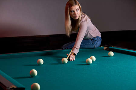 woman playing snooker game, preparing aiming to shoot pool balls on a billiards table, sitting on it