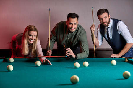 group of people or friends playing fun billiards, snooker or pool together, enjoy leisure time. fun, billiards, leisure, rest concept