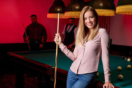 pretty woman in the bar next to billiards table pool, people playing snooker in the background. portrait Archivio Fotografico - 162157377