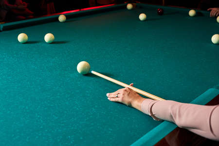game of billiards the hand of woman with a billiard cue aims at a billiard ball. sport game billiard
