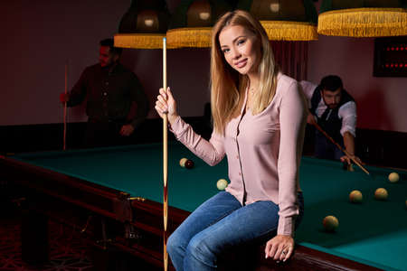 portrait of blond female sitting on billiard table posing, wearing casual outfit, in the bar, spending pleasant time, holidays