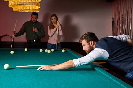 man is playing snooker, he is aiming to shoot the snooker ball. handsome guy holds hands on snooker table. billiards Archivio Fotografico - 162157380