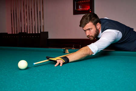 man holding arm on billiard table, playing snooker game or preparing aiming to shoot pool balls. sport game snooker billiards Archivio Fotografico - 162157381