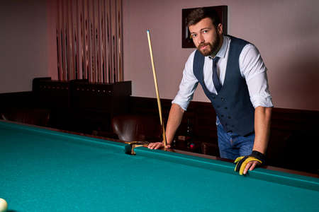 male standing next to billiards table, looking at camera, posing, in formal wear. portrait