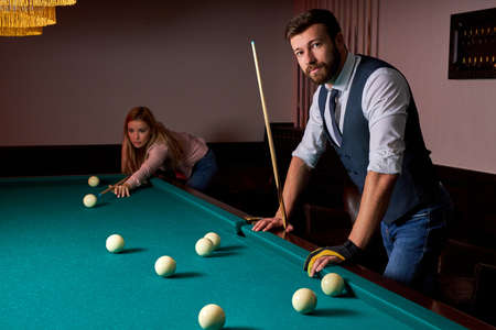 young active friends are playing billiards in bar after work, have rest and leaisure time, preparing aiming to shoot pool balls Archivio Fotografico - 162157383