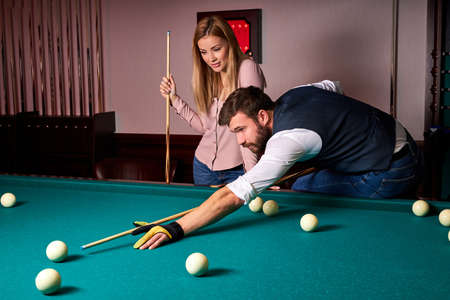 man leaning over the table while playing snooker, he is concentrated on game, having leisure time with girlfriend