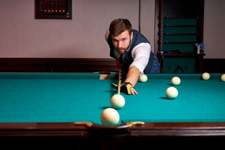 man is playing snooker, young male is aiming to shoot the snooker ball. handsome guy holds hands on snooker table. billiards