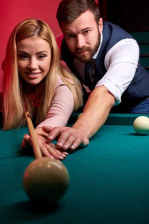 man teaching his girlfriend to play snooker, showing her how to aim the ball on billiards table