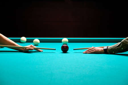 snooker - close-up shot of a two men playing billiard, aiming at ball on billiards table