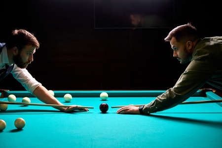 two young male friends came to play sport game billiards or snooker, in the dark club after work Archivio Fotografico