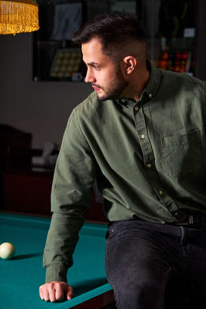 male in casual wear sits on billiards table, looking at game, snooker sport game concept. portrait Archivio Fotografico