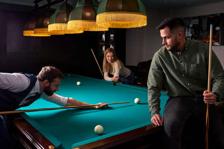 two young male friends came to play sport game billiards or snooker, in the dark club after work Archivio Fotografico - 162157345