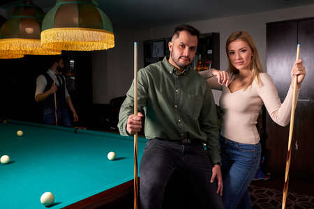 couple standing near the pool billiard table, they look at camera posing after game. leisure time