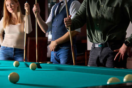 cropped people standing, playing fun billiards, snooker or pool together, enjoy leisure time. fun, billiards, leisure, rest concept