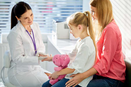 girl patient at usual medical inspection checkup, friendly affable doctor and patient in clinic, female pediatrician holding hand of girl, smile. medicine, healthcare concepts Archivio Fotografico