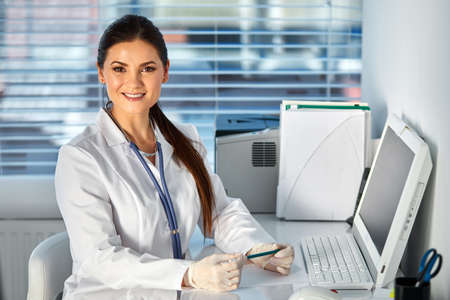 female doctor using pc computer while sitting at work place, posing at camera, she is is a working place of physician. healthcare, insurance and medicine concept