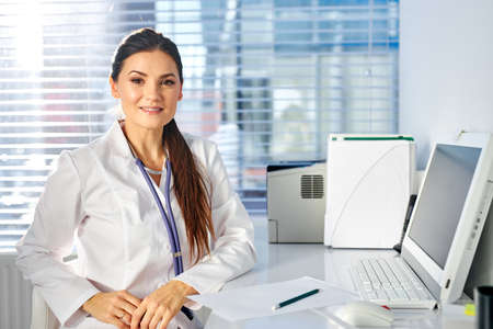 female pediatrician sitting at work place posing looking at camera, smiling, having stethoscope on neck. medicine and healthcare concept Archivio Fotografico
