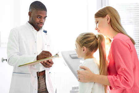 black male doctor talking to child and his mother during health checkup at the clinic, mom and girl get consultation by professional pediatrician or general practitioner during visit to the hospital