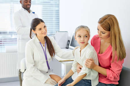 doctor talking to child and his mother during health checkup at the clinic, mom and girl get consultation by professional pediatrician or general practitioner during visit to the hospital Archivio Fotografico