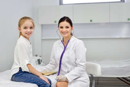 portrait of cheerful kid girl patient and female doctor posing at camera, sit smiling. child visit pediatrician. in hispital. medicine and healthcare concept