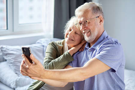 elderly couple taking photo on smartphone, while sitting in bedroom, sit smiling. senior people society lifestyle technology concept. man and woman share social media together in wellbeing home Archivio Fotografico