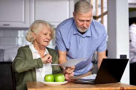 elderly man and woman managing family monthly budget together, focused married couple using computer banking application, counting bills in the kitchen Archivio Fotografico