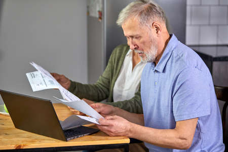 senior couple checking bills while managing accounts on home banking app. casual gray-haired man and woman using laptop while looking at invoice and plan the budget to save Archivio Fotografico - 162157198