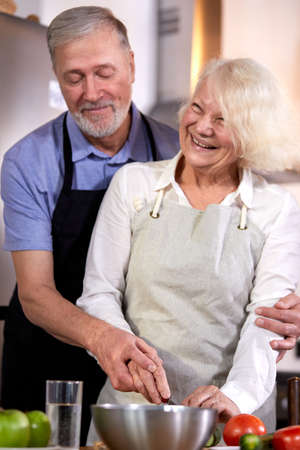 elderly couple preparing vegetable salad in kitchen, gray-haired handsome man helps wife with cooking, going to have healthy breakfast. focus on hands Archivio Fotografico