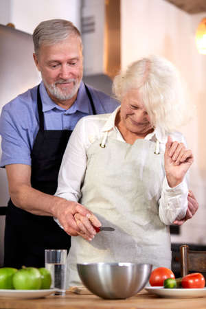 elderly couple preparing vegetable salad in kitchen, gray-haired handsome man helps wife with cooking, going to have healthy breakfast Archivio Fotografico - 162157201
