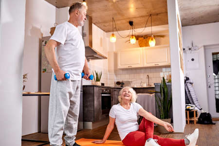 senior couple do exercises at home together, yoga and workout with dumbbells