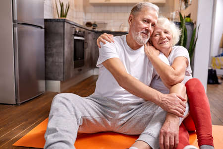 senior couple having rest on the floor after yoga exercises, in sportive wear, look at camera and smile Archivio Fotografico