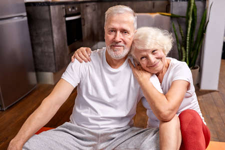 mature couple relax on the floor after gymnastics, look at camera smiling, woman hugs man Archivio Fotografico - 162157204