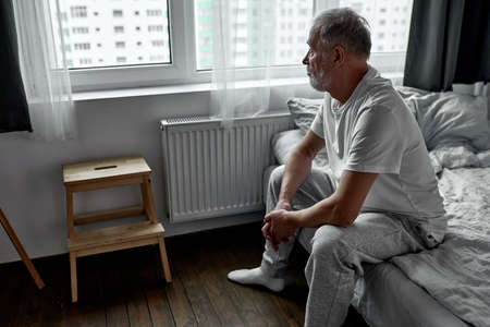 elderly man sitting alone at home, social distancing and self isolation in quarantine lockdown for Coronavirus