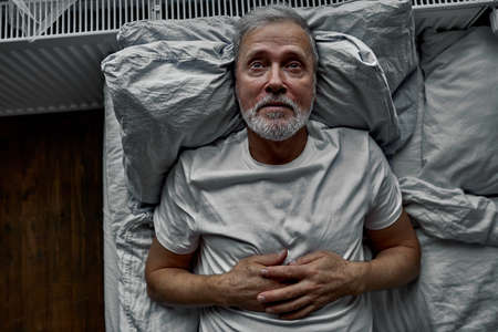 middle-aged man lying down in bed on pillow, having insomnia sleeping disorder. alone at home Archivio Fotografico