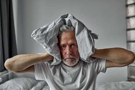 senior man goes crazy with insomnia, covers his ears with a pillow, tire and exhausted