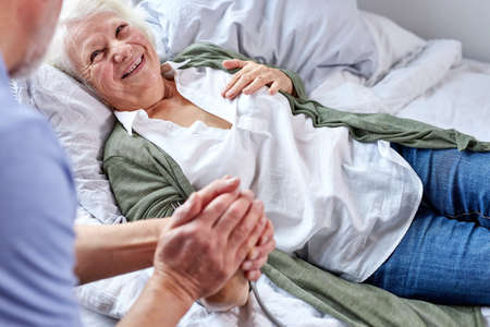 mature man supporting his sick wife lying on bed, woman is suffering from high pressure, female smile