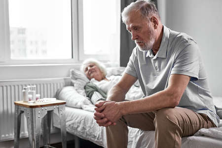 upset pensioner man sits in depression while her sick woman suffering from covid-19, he wants wife to be healthy Archivio Fotografico - 162157128