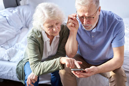 senior couple looking at childrens photos in smartphone, online surfung Net,modern technology concept. caucasian woman and man using mobile phone share social media together in wellbeing home.