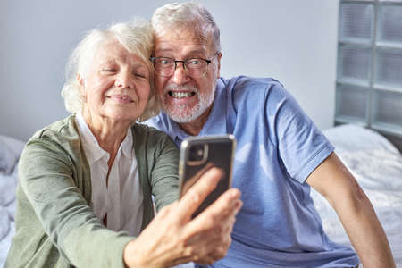 elderly couple sitting on a couch taking photo on smartphone, posing at phones camera, enjoying time at weekends. family, technology, age and people concept