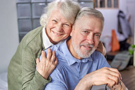 60s elderly couple relaxing at home, posing looking at camera smiling capture moment for family album photo shooting indoors, grey-haired grandparents eternal love Archivio Fotografico