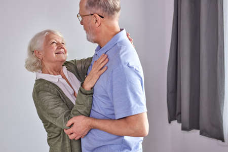 senior couple dancing in living room, husband holding hand of mature wife enjoying fun together, spend holidays, leisure retirement ifestyle at home. in casual domestic wear Archivio Fotografico - 162157134