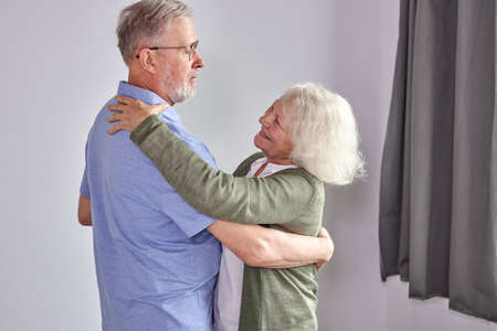 senior couple dancing in living room, husband holding hand of mature wife enjoying fun together, spend holidays, leisure retirement ifestyle at home. in casual domestic wear Archivio Fotografico - 162157135