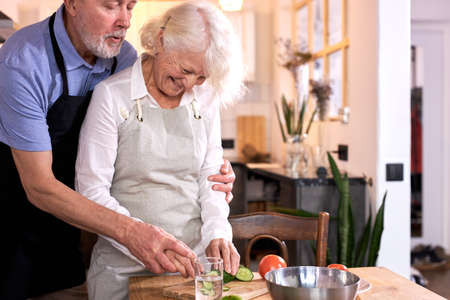 couple having fun in kitchen with healthy food, cooking meal at home, preparing lunch with bio fresh vegetables, carving or cutting vegetables, man helps his wife, wearing apron