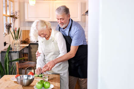 mature woman preparing meal, her husband help her from back, carving vegetables
