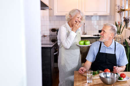 senior man carving vegetables and wife holding plate with apples, cook together, enjoy being healthy. at home