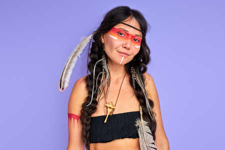 young ethnic lady with feathers on her head isolated over purple background, female in top posing at camera, shaman smiles