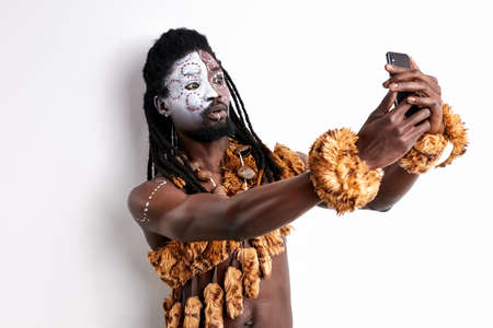 misunderstanding african tribal use mobile phone, try to study its camera, having ethnic paintings on face, isoalted on white