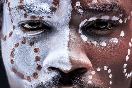 black male with national ethnic make-up on face, pagan eyes look at camera close-up
