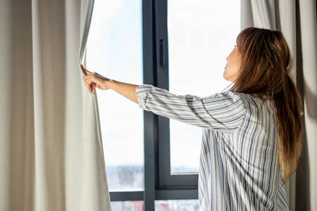 female opening the curtains in the morning after waking up, in pajamas
